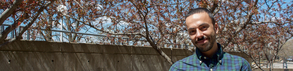 Photo of UMN employee standing outdoors under a tree smiling at the camera