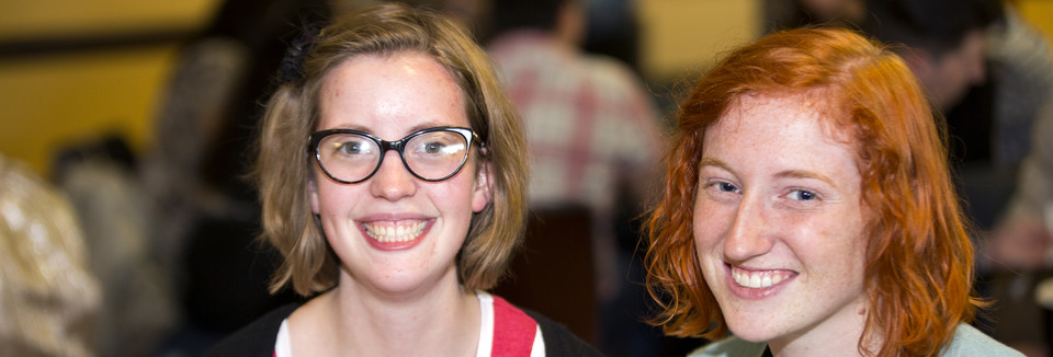 Photo of 2 students laughing and smiling into the camera