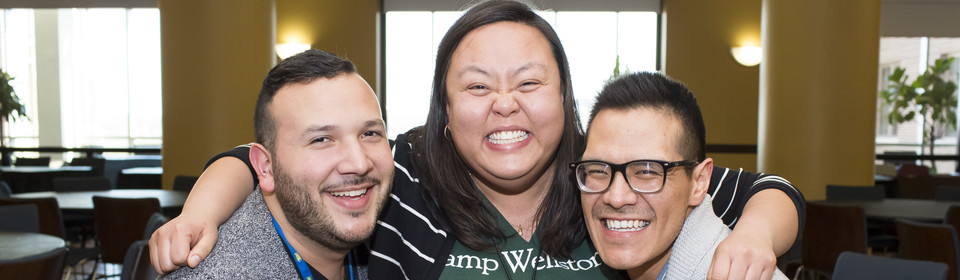 Photo of 3 people hugging side by side and smiling for the camera