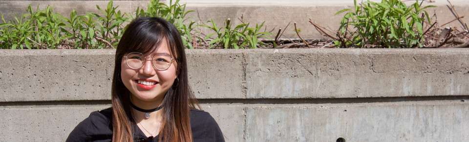 Photo of student smiling for the camera against a wall outdoors