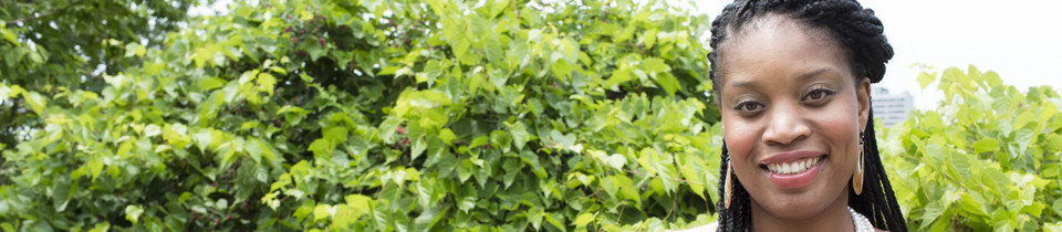 Photo of UMN Staff member outdoors standing next to a wall of ivy