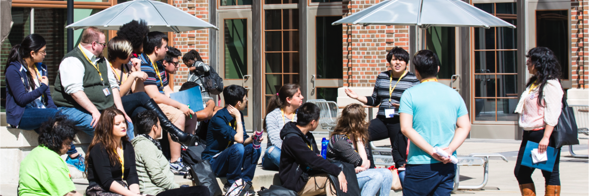 Photo of students from the 2014 Queer, Indigenous People and People of Color Conference sitting outside for a workshop